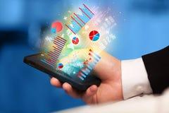 Smartphone della tenuta dell'uomo di affari con i simboli del grafico Fotografie Stock Libere da Diritti