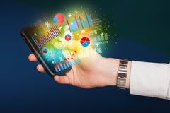 Smartphone della tenuta dell'uomo di affari con i simboli del grafico Immagine Stock Libera da Diritti