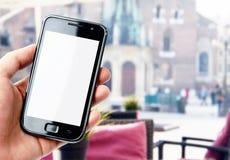 Smartphone della tenuta della mano in caffè della città Immagini Stock