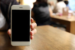 Smartphone della tenuta della mano con il backgound della gente Fotografia Stock Libera da Diritti