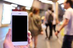 Smartphone della tenuta della mano con il fondo della gente Fotografia Stock