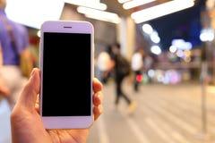 Smartphone della tenuta della mano con il fondo della gente Fotografia Stock Libera da Diritti