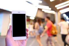 Smartphone della tenuta della mano con il fondo della gente Immagini Stock