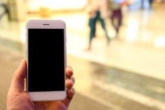 Smartphone della tenuta della mano con il fondo della gente Fotografie Stock Libere da Diritti