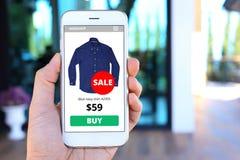 Smartphone della tenuta della mano con il sito Web dello schermo di commercio elettronico Fotografia Stock Libera da Diritti