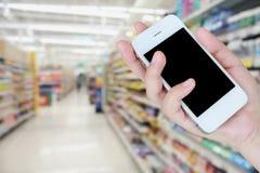 Smartphone della tenuta della mano con il supermercato Fotografie Stock Libere da Diritti