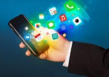 Smartphone della tenuta della mano con le icone variopinte di app Fotografia Stock