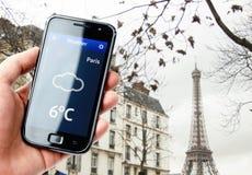 Smartphone della tenuta della mano con tempo a Parigi Fotografie Stock