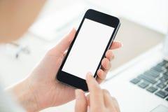 Smartphone della tenuta della persona con lo schermo in bianco
