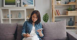 Smartphone della tenuta della giovane donna che esamina schermo e che scrive in taccuino stock footage