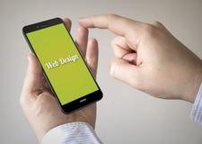 Smartphone dello schermo attivabile al tatto con web design sullo schermo Fotografia Stock Libera da Diritti