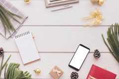 Smartphone dello schermo in bianco con la composizione in Natale sulla tavola, sul fondo di legno bianchi del buon anno e di Buon immagini stock