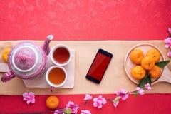 Smartphone dello schermo in bianco con la teiera e la tazza di tè, frutta arancio sul fondo rosso della tovaglia immagine stock libera da diritti