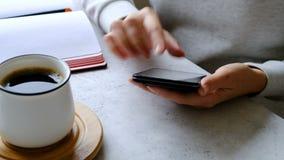 Smartphone in den Händen, im Kaffee und im Notizbuch der Frau auf einer Tabelle Abschluss oben stock video