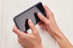 Smartphone in den schönen weiblichen Händen Lizenzfreie Stockbilder