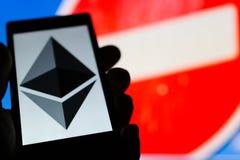 Smartphone in der Hand mit Ethereum-cryptocurrency Logo Prohibitin Lizenzfreie Stockfotografie