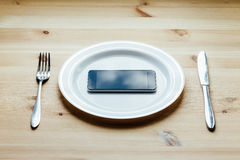 Smartphone an der leeren Platte Lizenzfreies Stockfoto