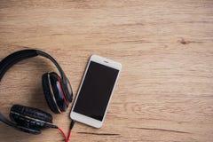 Smartphone des leeren Bildschirms mit Kopfhörer auf Holztisch Beschneidungspfad eingeschlossen Lizenzfreie Stockfotografie