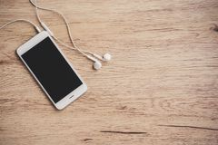 Smartphone des leeren Bildschirms mit Kopfhörer auf Holztisch Beschneidungspfad eingeschlossen Lizenzfreie Stockfotos