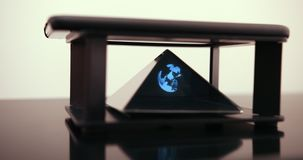 The Smartphone Designs A Hologram Of Earth For A Special Prism That Is On A Hologram Table. Prores 4k. The Smartphone Designs A Hologram Of Earth For A Special stock video footage