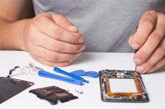 Smartphone desmontado fixação do reparador com ferramentas especiais e chaves de fenda conceito de dispositivos do reparo da elet imagem de stock royalty free