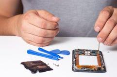 Smartphone desmontado fixação do reparador com ferramentas especiais e chaves de fenda conceito de dispositivos do reparo da elet foto de stock royalty free