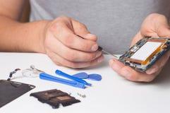 Smartphone desmontado fixação do reparador com ferramentas especiais e chaves de fenda conceito de dispositivos do reparo da elet imagens de stock royalty free
