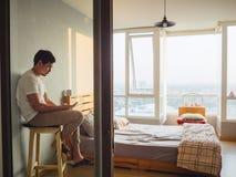 Smartphone di chiacchierata dell'uomo solo e caffè bevente nella sua stanza a fotografie stock