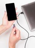 Smartphone di collegamento della donna ad un taccuino per alimentare Immagine Stock