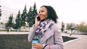 Smartphone di conversazione della ragazza attraente della corsa mista e passeggiate beventi del caffè in via della città con le b immagine stock libera da diritti