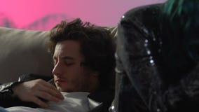 Smartphone di scorrimento della donna, uomo con Male di sensibilità di postumi di una sbornia dopo il partito domestico archivi video