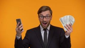 Smartphone di sguardo maschio ed immediatamente ricevere applicazione dei contanti dei soldi indietro archivi video