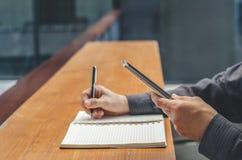 Smartphone di uso dell'uomo d'affari mentre facendo le note in taccuino Studente che impara online Uomo che per mezzo dell'aggegg Immagini Stock Libere da Diritti