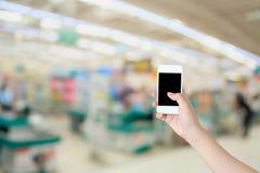 Smartphone di uso della mano con il fondo del deposito del supermercato Fotografia Stock Libera da Diritti