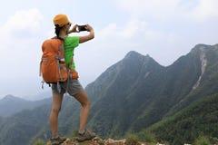 Smartphone di uso di viaggiatore con zaino e sacco a pelo della donna sulla montagna Fotografie Stock Libere da Diritti