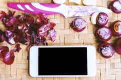 Smartphone di vista superiore con la raccolta delle cipolle e dei chilis freschi Immagini Stock Libere da Diritti