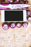 Smartphone di vista superiore con la raccolta delle cipolle e dei chilis freschi Fotografia Stock