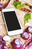 Smartphone di vista superiore con la raccolta delle cipolle e dei chilis freschi Immagine Stock Libera da Diritti