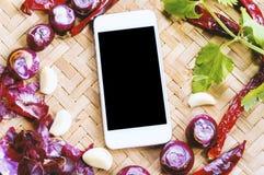 Smartphone di vista superiore con la raccolta delle cipolle e dei chilis freschi Immagini Stock