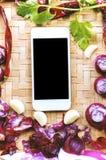 Smartphone di vista superiore con la raccolta delle cipolle e dei chilis freschi Immagine Stock