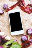 Smartphone di vista superiore con la raccolta delle cipolle e dei chilis freschi Fotografie Stock