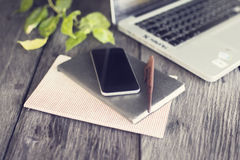 Smartphone, diary, pen and laptop on wooden table outdoor Royalty Free Stock Images