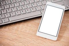Smartphone die op laptop toetsenbord leggen stock afbeeldingen
