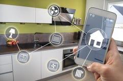 Smartphone in dient een keuken in stock afbeelding