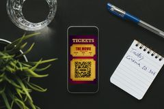 Smartphone with digital cinema tickets in the screen, and notebook with handwritten text. Electronic cinema tickets in a mobile phone screen Stock Photos