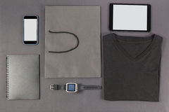 Smartphone, digital tablet, diary, folded t-shirt, shopping bag and watch Stock Photos