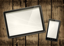 Smartphone and digital tablet PC on a dark wood table. Horizontal office mockup Royalty Free Stock Photo