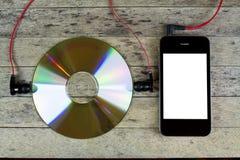Smartphone, disco do CD, fones de ouvido Fotografia de Stock Royalty Free