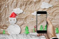 Smartphone disponível com tela vazia, papel amarrotado cortou o boneco de neve no inverno, com espaço da cópia na tela imagens de stock
