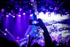 Smartphone ? disposition ? un concert, lumi?re bleue d'?tape image stock